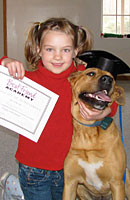 Small girl with dog and graduation certificate